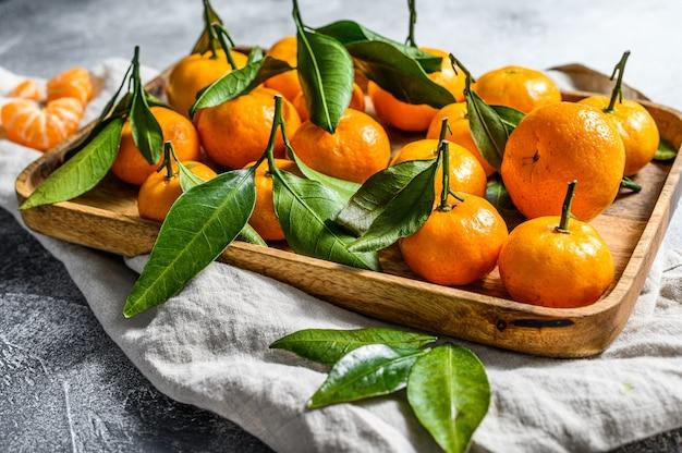 Мандарины (апельсины, мандарины, клементины, цитрусовые) с листьями в деревянной миске. серый фон вид сверху