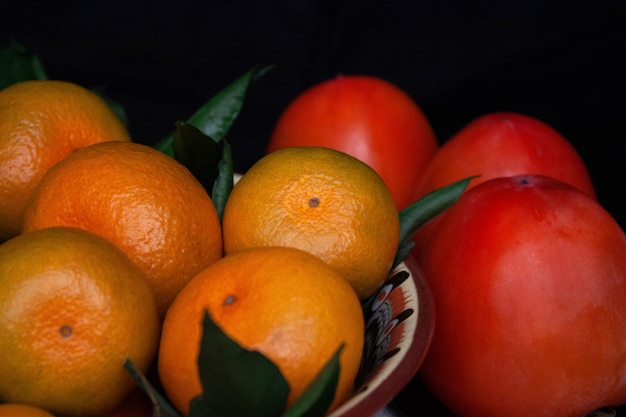 Tangerines and persimmons lie on a beautiful dish close-up on a black background.