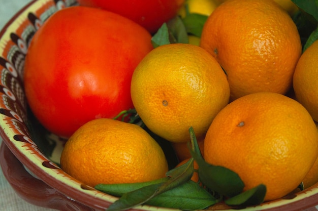 Tangerines and persimmons lie on a beautiful dish close-up.