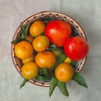 Tangerines and persimmons lie on a beautiful dish.