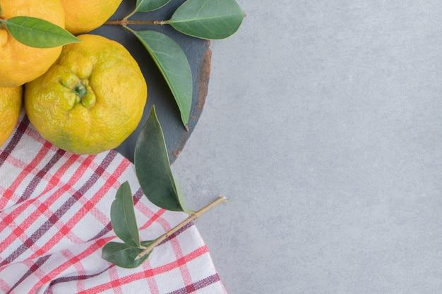 Mandarini ammucchiati su un asciugamano su una tavola di legno, su marmo.