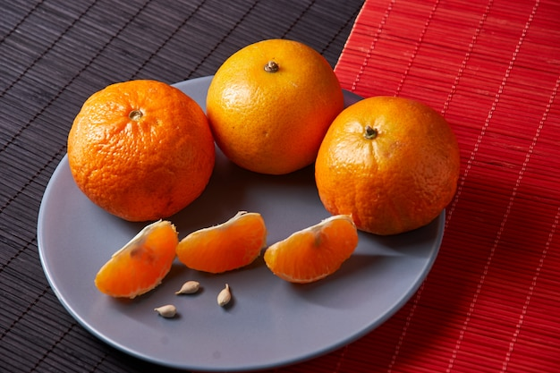 Tangerines in plate on black and red surface