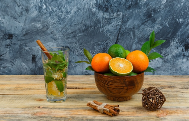 Tangerines in pot with detox water and cinnamon on wooden board