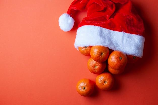 Tangerines in a santa hat on an orange background