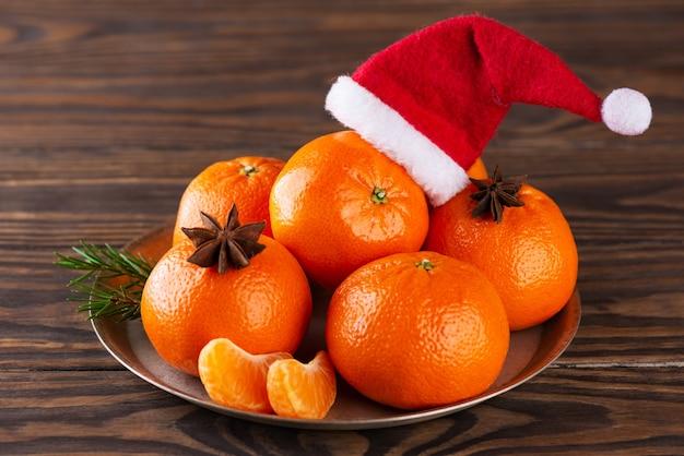 갈색 나무 테이블에 아니스와 산타클로스 모자를 쓴 귤