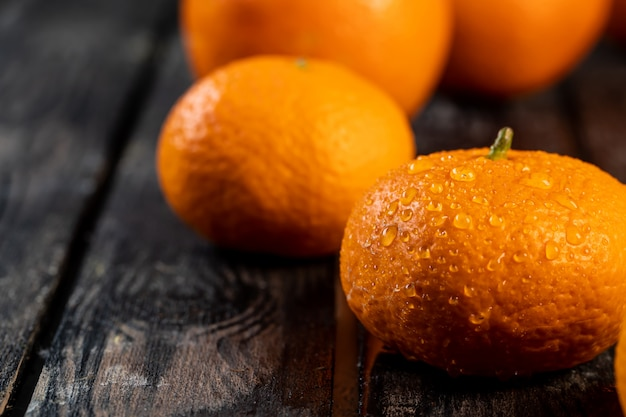 Tangerines with drops of water on a wooden table