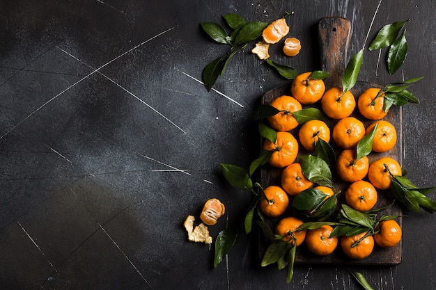 Tangerines with green leaves on wood board on dark