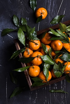 Tangerines with green leaves in wood box on dark
