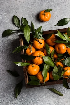 Tangerines with green leaves in wood box on light