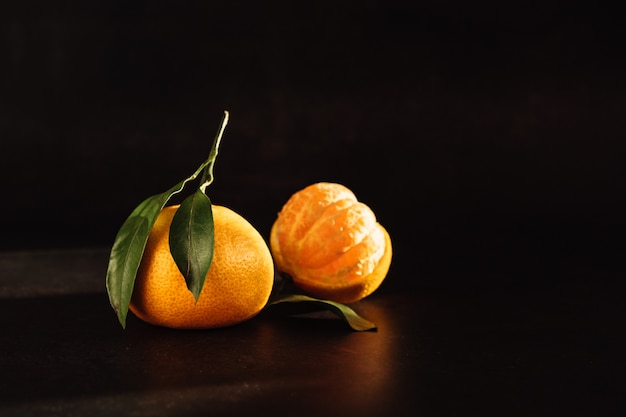Tangerines with leaves in the dark