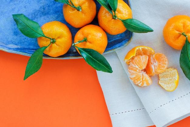 오렌지 배경에 파란색 접시에 잎 감귤. 크리스마스 음식의 상징, 공간의 사본