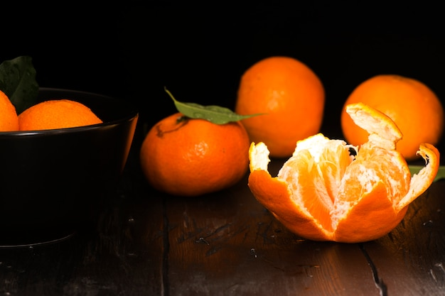 Tangerines with leaves on old dark wooden table