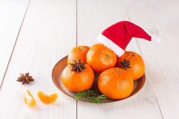 크리스마스와 새해 밝은 나무 테이블에 산타클로스 모자와 아니스가 있는 귤