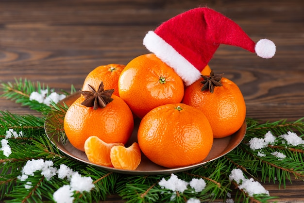 갈색 나무 테이블에 산타클로스 모자와 전나무 가지가 있는 귤