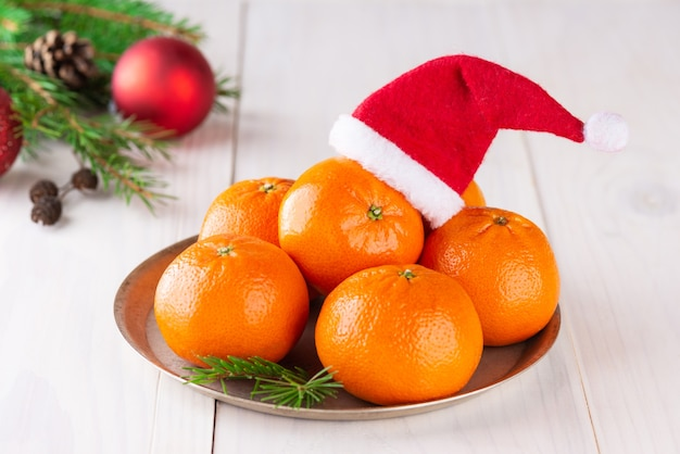 크리스마스 공이 있는 가문비나무 가지가 있는 나무 테이블에 산타클로스 모자를 쓴 귤