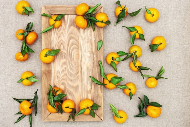 Tangerines with wooden board on sackcloth