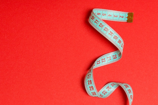 Tangled measuring tape with space for your idea. sewing and tailor concept on red background.