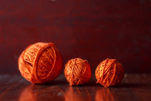 Tangles of orange threads for knitting lie on a wooden table.