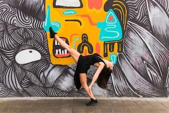 Tango female dancer posing against creative graffiti wall