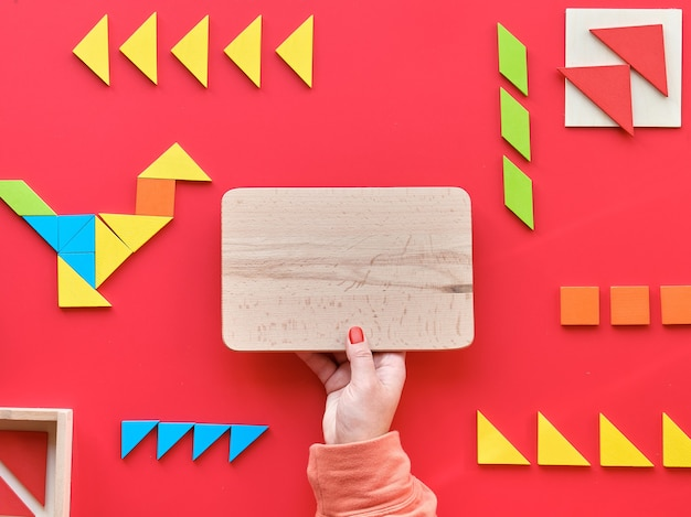 Tangram elements scattered and arranged in pictogram. hand hold wooden blank board