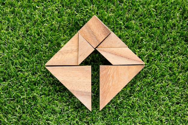 Tangram puzzle as arrow in square shape on wooden background