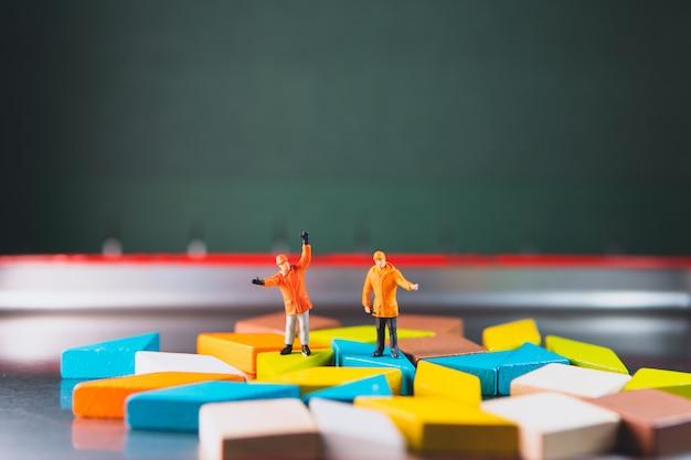 Миниатюрные люди, пара инженеров, стоящих с головоломкой tangram, используя концепцию бизнеса, логистики и промышленности