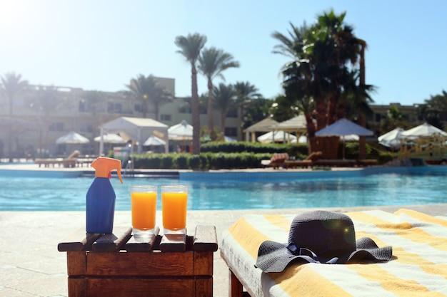 리조트 수영장 근처에 파란색 밀짚 모자를 쓰고 해변 탁자에 있는 태닝 로션 주스