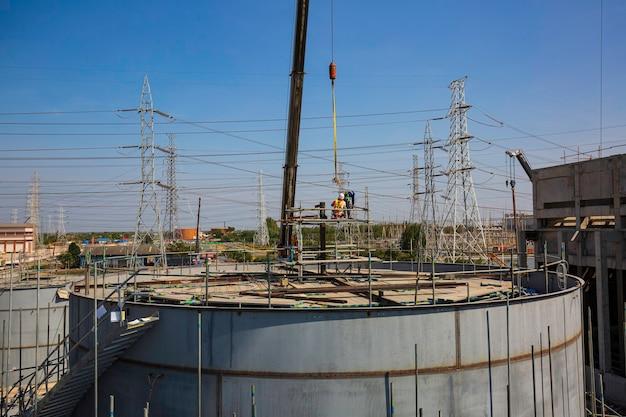 石油・ガス産業発電所の大型クレーンリフト建設機械のタンク建設現場で、足場の作業員がいる
