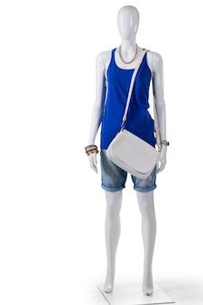 탱크탑과 흰색 핸드백. 흰색 지갑을 착용하는 여성 마네킹입니다. 평범한 흰색 가죽 가방. 지역 상점에서 저렴한 의류.
