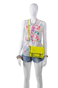 라임 지갑이 달린 탱크탑. 라임 가방을 입고 여성 마네킹입니다. 다채로운 핸드백과 여름 복장입니다. 어린 소녀를 위한 세련된 모습.