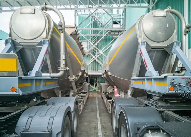 Tanker storage truck loading sugar in storage silo at manufacturing factory.