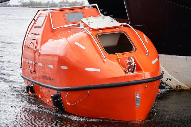 Tanker version fire resistant totally enclosed lifeboat float near big vessel
