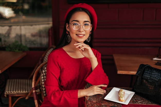 Tanned asian woman in red beret, bright dress and eyeglasses smiles, sits in gorgeous cafe and looks into camera