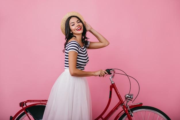 Signora beata abbronzata con cappello divertendosi con la bicicletta. ritratto dell'interno della ragazza di buon umore in lussureggiante gonna in piedi.