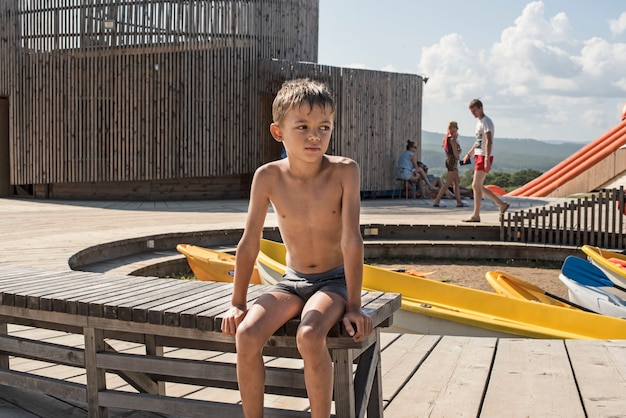 The tanned boy sitting on the bench at the boat station.