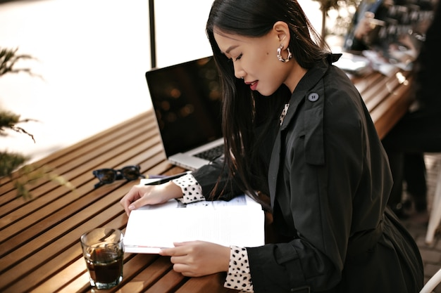 Tanned brunette asian woman in black trench coat smiles, sits at wooden desk with glass of coffee and reads book outside