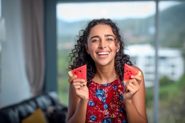 검게 그을린 갈색 머리는 그녀의 손에 신선한 빨간 수박을 즐깁니다.