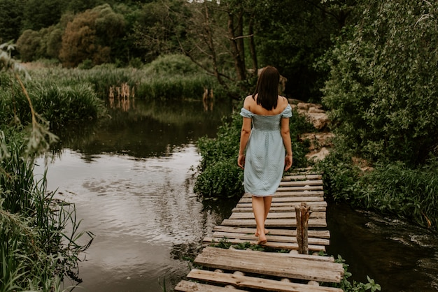 A tanned brunette girl in a turquoise dress walks across the river alone an old wooden bridge.