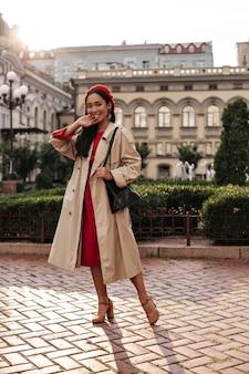 미디 레드 드레스, 세련된 베레모, 베이지색 트렌치 코트를 입은 검게 그을린 갈색 머리 여성이 활짝 웃고 밖에서 포즈를 취합니다.