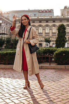 Tanned brunette woman in trendy trench coat, red dress and bright stylish beret waves hand in greeting, smiles, holds black handbag and poses outside