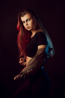 세련 된 옷을 입고 스튜디오에서 포즈를 취하는 예술 화장을 한 검게 그을린 갈색 머리 여자