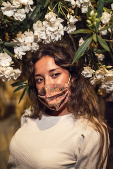 Donna caucasica abbronzata che indossa una maschera floreale in un parco di divertimenti