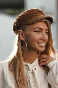 갈색 벨벳 모자와 흰색 면화 블라우스에 검게 그을린 매력적인 여자가 진심으로 미소 짓고 밖에서 포즈를 취합니다.