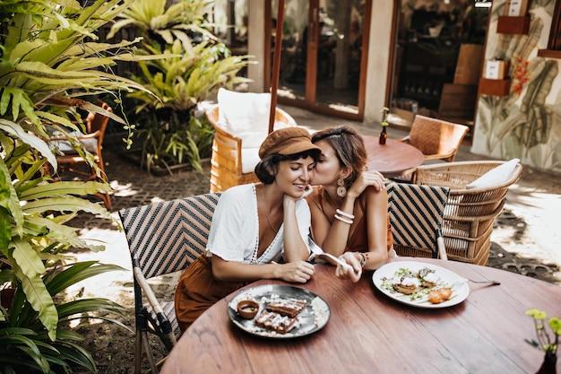 スタイリッシュな夏の装いで日焼けした陽気な女性がゴシップをし、ストリートカフェでおいしい料理を楽しむ