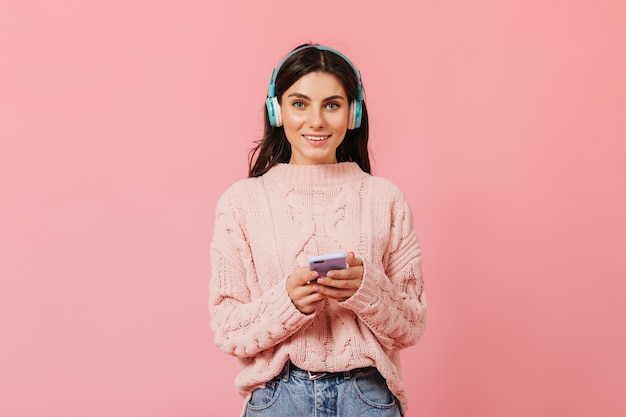 Загорелая темноволосая девушка с очаровательной улыбкой смотрит в камеру. дама в наушниках переключает песню на телефоне.