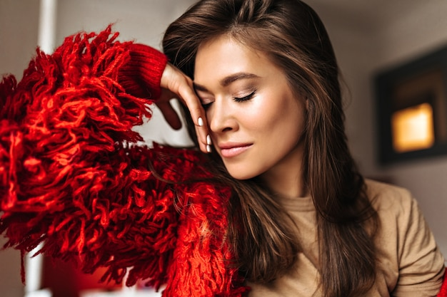 Tanned dark-haired woman in beige t-shirt leaned against wall. portrait of attractive lady wearing red jacket.