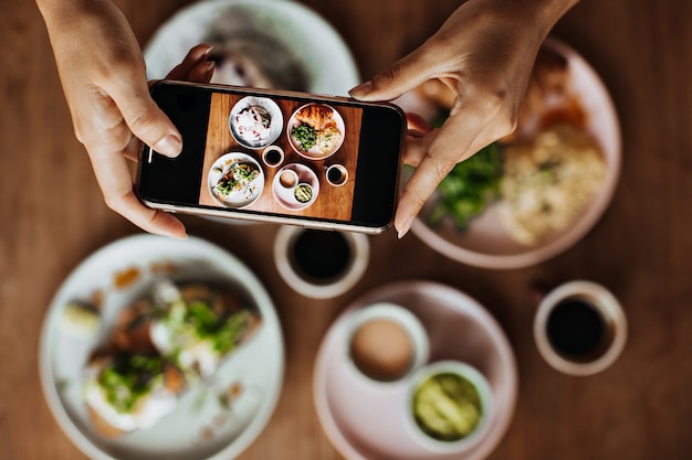Tanned female hands holding smartphone and taking photos of plate with meal