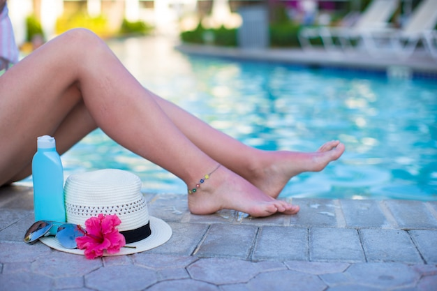Tanned female legs near pool with sunscreen and hat