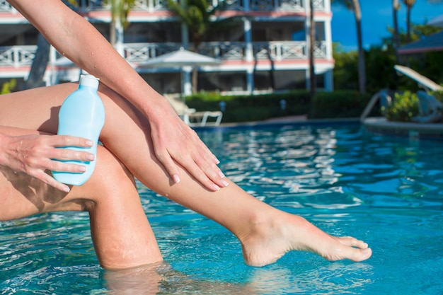 Tanned female legs near swimming pool with sunscreen