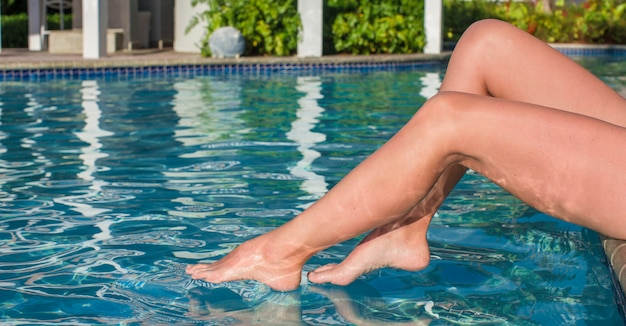 Tanned female legs near swimming pool